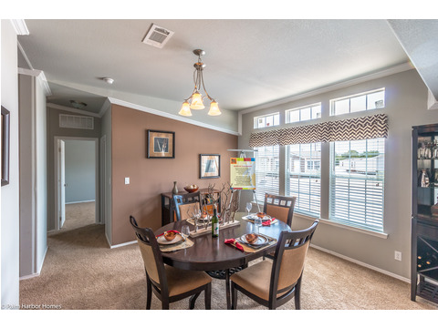 The separate dining area is flooded with natural light and adjacent to the kitchen for easy service in the Hacienda by Palm Harbor Homes - 4 Bedrooms, 3 Baths, 2338 Sq. Ft.