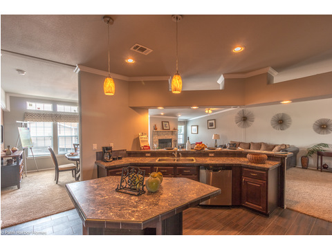 The person working in this kitchen can be part of a any conversation in the open concept living area of the Hacienda SCWD60T5 by Palm Harbor Homes