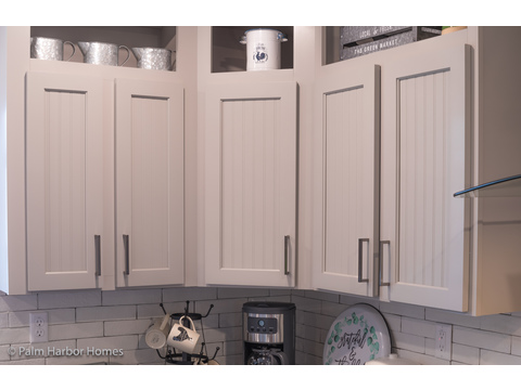Beautiful Shaker cabinetry with bead board insets in dove grey. From the kitchen to the dining area in the Vintage Farmhouse Model with 3 Bedrooms, 2 Baths and 1,984 Sq. Ft. Exterior Dimensions: 31 x 64. Other layouts available from Austin TX