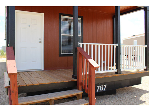 The built-in, covered porch on the 880-square foot Hibiscus manufactured home by Palm Harbor Homes makes it perfect for downsizing, guest house, vacation house, hunting cabin and more!