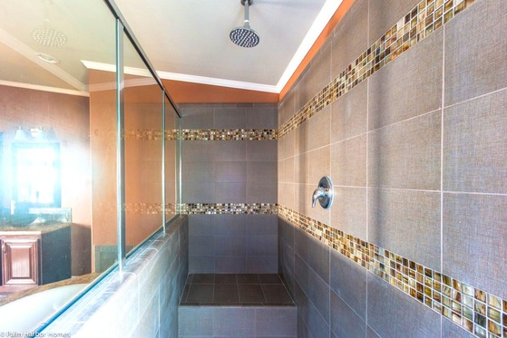 tiled walk in shower with waterfall head