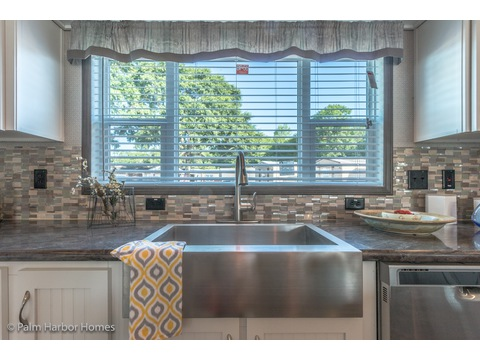Great views from this large window in the kitchen. Love the stainless farm sink  pull out faucet in this Carrington 74 ML30744C, 2,220 square feet, 4 bedroom bath - 2 living areas - 1 dining area - double wide manufactured home by Palm Harbor Homes.