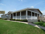 Exterior view of The Evolution manufactured home model SCWD76X3 by Palm Harbor Homes - shown with full built-in porch option