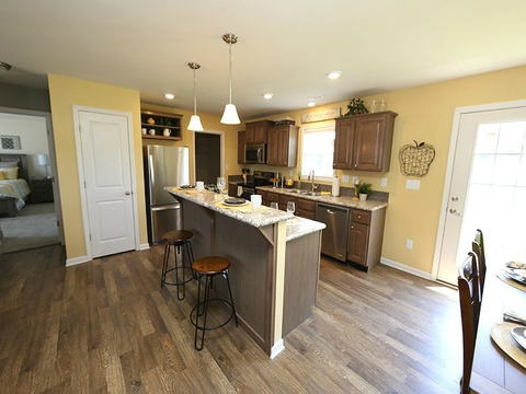 Great kitchen with island and open living concept to dining area in the Drake - a 4 Bedroom, 2 Bath, 1,882 Sq. Ft. modular Palm Harbor home built by Nationwide Homes