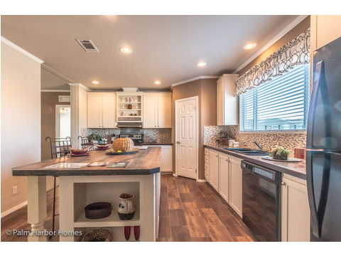 The well-designed kitchen features a large island but does not feel crowded.  The island provides acres of prep space and storage as well as areas for displaying collectibles or recipe books. - The Harbor House FTP360M6 Palm Harbor Homes