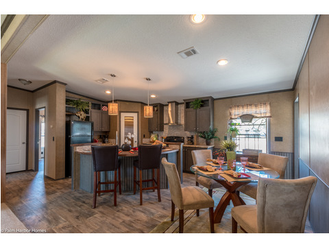 Open kitchen with an eat-in island bar and attached dining room area for family dinners - in The Homeland model ML30483H manufactured home by Palm Harbor Homes with 3 Bedrooms, 2 Baths, 1,440 Sq. Ft.