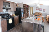 Island kitchen opening to living room with optional entertainment built-ins - The Home Box Office by Palm Harbor Homes