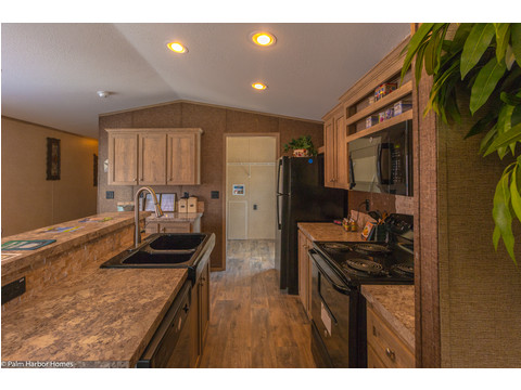 The kitchen on the Cabana III manufactured home by Palm Harbor has direct access from the living room and from the kitchen with a sit down serving bar and plenty of storage. - Palm Harbor Homes