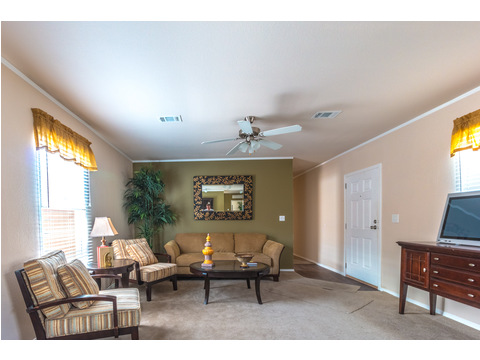 Spacious living room with windows on both sides in The Woodland II by Palm Harbor Homes - 3 Bedrooms, 2 Baths, 1,116 Sq. Ft.
