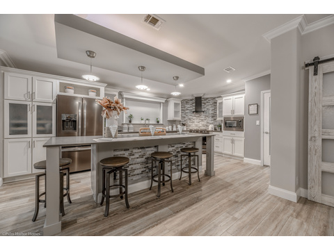 The kitchen is dramatically set off from the rest of the open living area by the huge island & light feature - La Belle IV X4769H in Florida - 4 Beds, 3 Baths, 2,847 Sq. Ft. triple wide manufactured home or modular home by Palm Harbor Homes