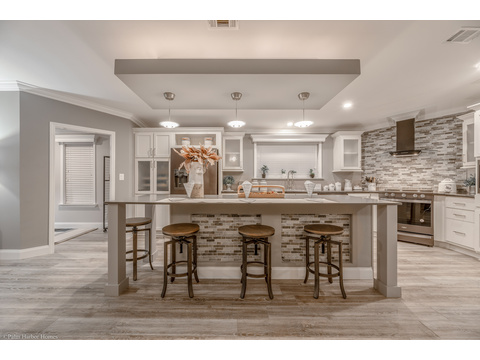 The kitchen is just steps from the other rooms of the home, but the bar serves to create the space - the La Belle IV X4769H in Florida - 4 Bedrooms, 3 Baths, 2,847 Sq. Ft. triple wide manufactured home or modular home by Palm Harbor Homes