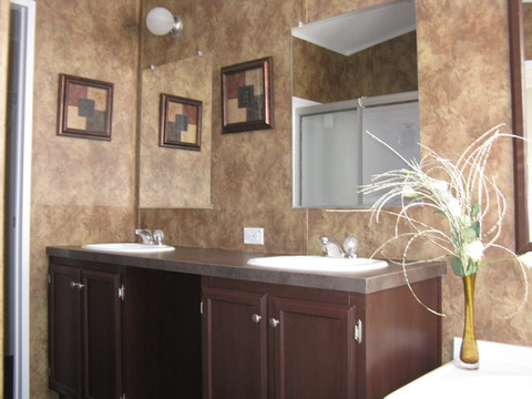 The Slant Kitchen home by Palm Harbor Homes has a charming master bathroom! Dual vanities offer more space for two on those hectic mornings. And yes that is a glimpse of a stand up shower in addition to the glamour bath (mirror)!