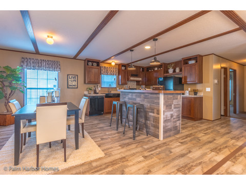 View of the dining area and the kitchen from the living area of the Velocity Model 32523V - a double wide manufactured home available from Palm Harbor Homes