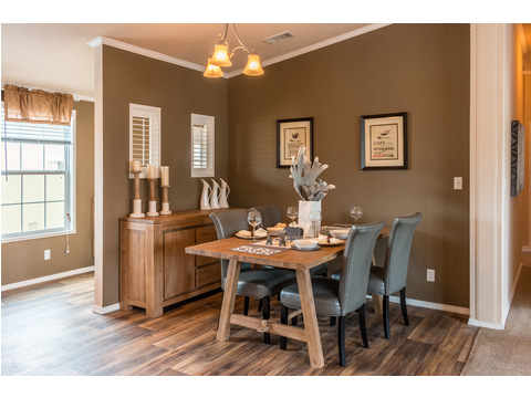 Beautiful dining room... tile floors, natural light, wall space for a china hutch or artwork, and open to both kitchen and living room! The wall you see behind the table leads to the utility/mud room. - The Canyon Bay II HHT476A5 by Palm Harbor Homes