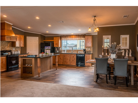 A view from the living into the kitchen/dining area!  The island is massive & seats 4 comfortably! The dining area is large enough to fit a table for eight! Tons of counter and cabinet space too. The Canyon Bay II HHT476A5 by Palm Harbor Homes