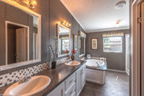 Luxury Master Bathroom features plywood drawers on stainless ball-bearing guides, His and Hers china sinks with Moen faucets. Deep soaking bathtub with formica water sealed platform. Walk-in shower with bench seats. Elements Tile Flooring!